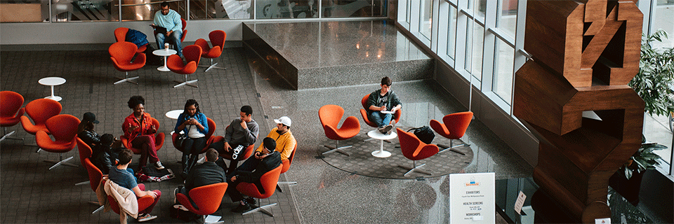 Students sitting in a circle and conversing in the campus center.