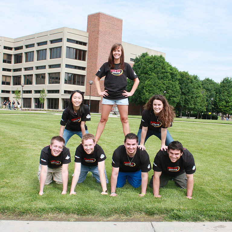 Students on the OTEAM creating a human pyramid with their bodies in the middle of Taylor Hall courtyard in 2010.