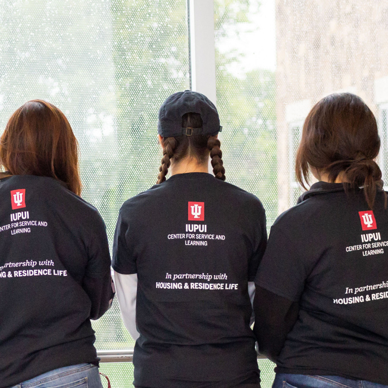 Three girls with their backs to the camera with shirts that say IUPUI Center for Service and Learning