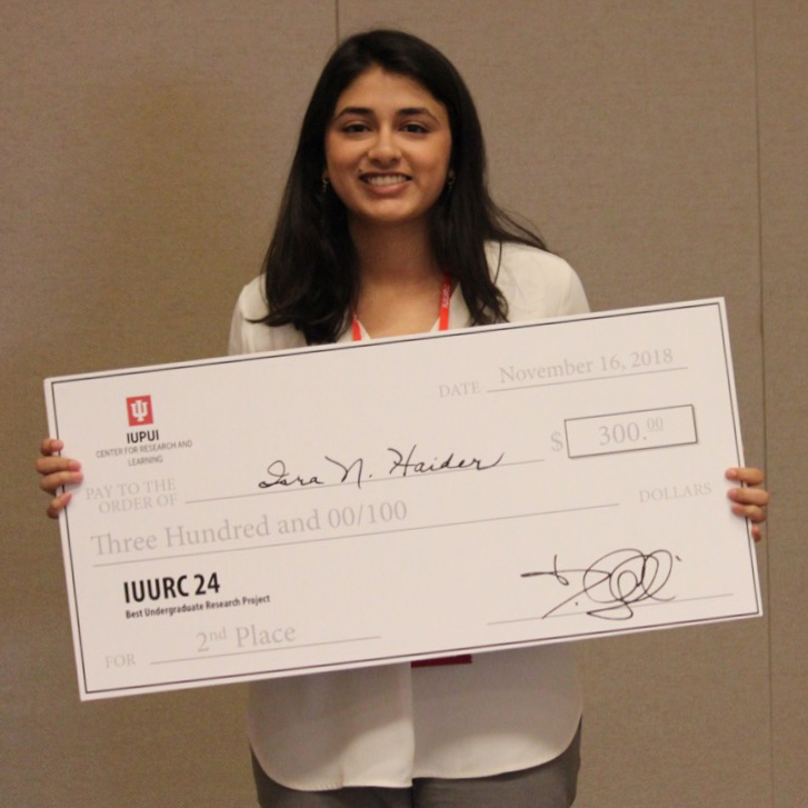 Woman holding her award check