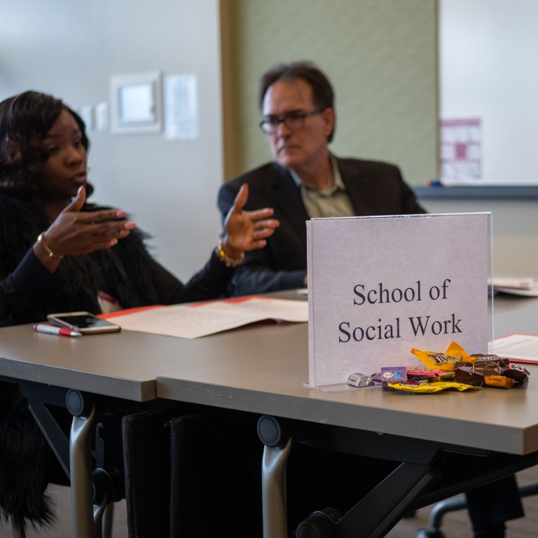 Woman at table talking to two other people, one who is not pictured, with a sign that says School of Social Work